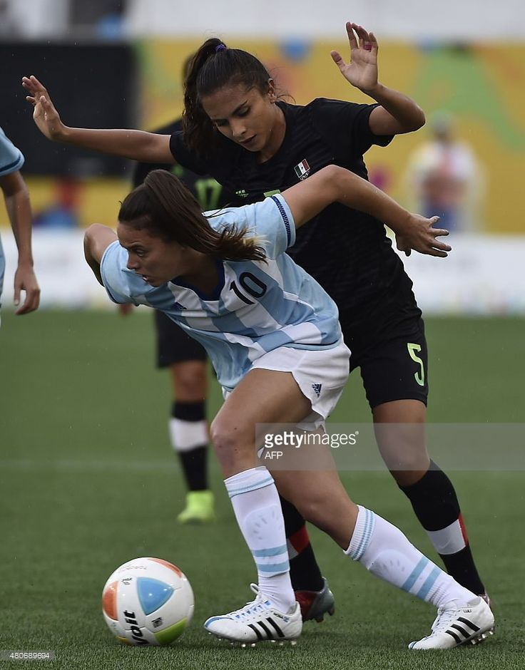July 14 - Football - Women - First Round.  Mexico vs Argentina. Argentina's Florencia Bonsegundo (L) drives the ball past Valeria Miranda of Mexico during a women's first round group A football match of the Pan American Games in Hamilton, Canada, on July 14, 2015. AFP PHOTO / OMAR TORRES