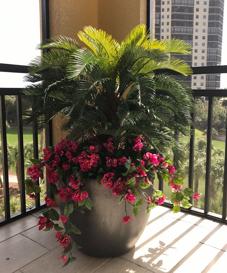 A cycas palm underplanted with fuschia bougainvillea looks gorgeous in this FL lanai corner. Both are outdoor artificial plants.