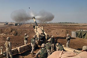 U.S. Marines from Mike Battery, 4th Battalion, 14th Marines, operate the 155mm M198 howitzer at Camp Fallujah, November 2004.