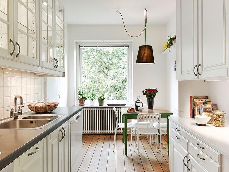 Cocina blanca luminosa. Vistas de árboles.