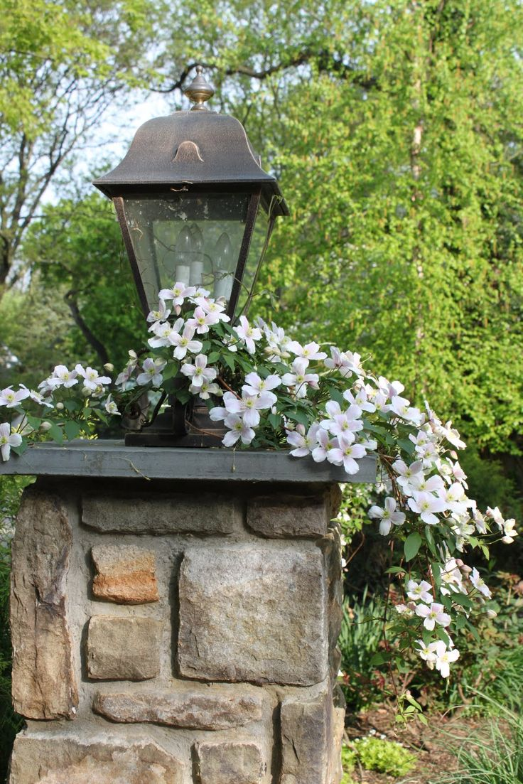 Stone entrance with lamp and clematis.  Structure is very important in design.  It invites you in with a sense of balance, peace and serenity.