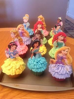 Disney Princess Cupcakes. Very cute!!  :)  I used kid's party cups with the princesses on them from Walmart - just cut out the images I wanted to use and glued cake pop sticks to the back. These were so fun to make. by angie