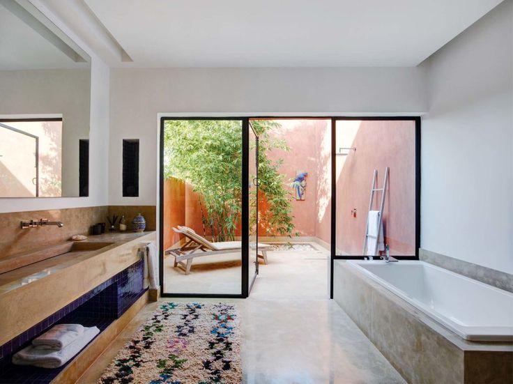El ritual del baño en el cuarto de esta suite resulta aún más reconfortante, gracias a la ducha instalada al aire libre, que se convierte en un gratificante patio, dotado de una cómoda tumbona a la sombra de un árbol. En el interior, el amplio espacio acoge una zona de bañera y un gran lavabo de obra, cuyo frente se ha revestido de azulejos azules. La alfombra marroquí Beni Ourain, hecha a mano, introduce calidez en el suelo.