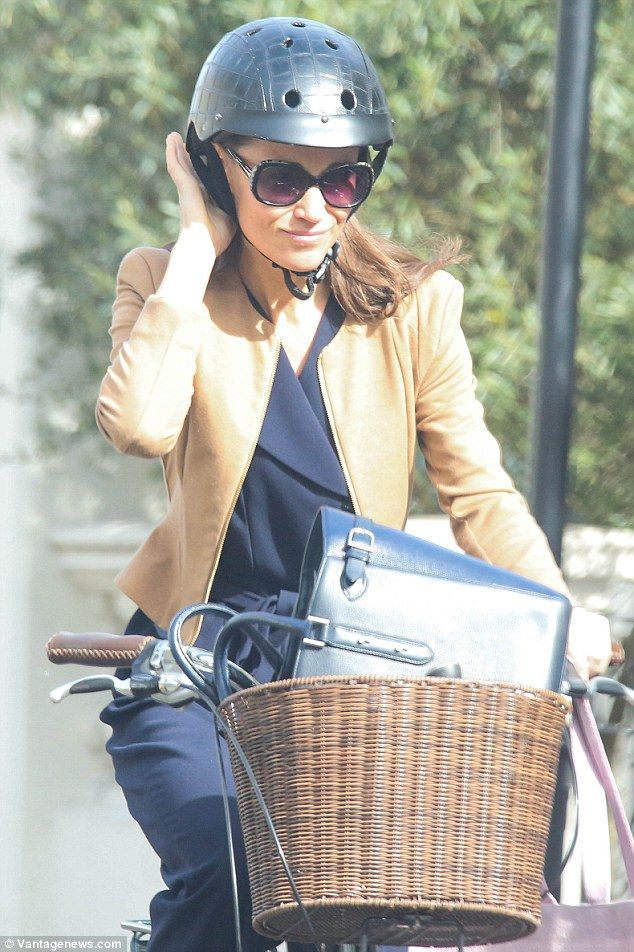 Pippa was today spotted with a large pink garment bag while cycling near her west London home - prompting royal watchers to wonder whether the bag provided a clue