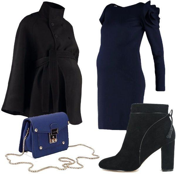 Mantella nera con bottoni, vestito elegante dark blue con rouches sulle spalle, stivaletti con tacco e nappina neri e tracollina blu con catenina dorata.