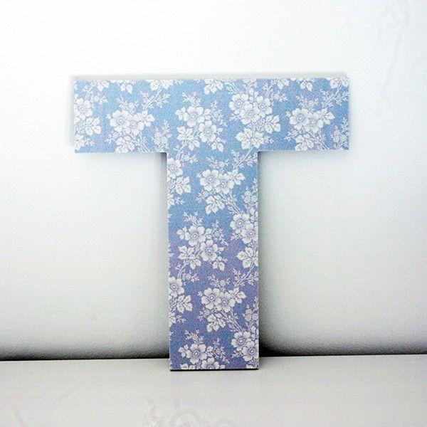 letras decorativas t con estampado de flores blancas con fondo azul claro en la parte frontal