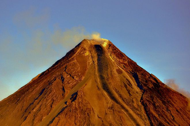 The conical summit of Mayon in the Philippines. Paths of previous lava flows and pyroclastic flows can be seen on the steep slopes of the volcano. Photo by Tryfon Topalidis / Wikimedia Commons.