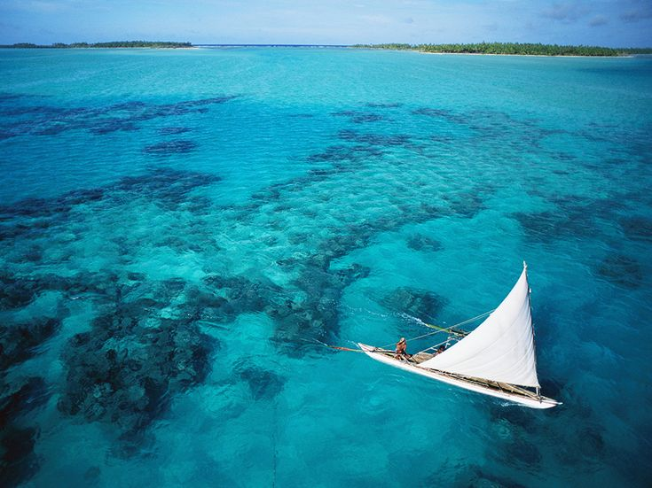 An outrigger skims the crystal-clear waters around the Republic of Kiribati's island of Tabiteuea [Photo by George Steinmetz, Corbis]