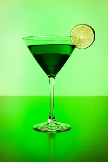 Shamrock Cocktail  Strobist:One Vivitar 285HV gelled green and pointed at the background. One Nikon SB-25 through white umbrella camera right. Black reflectors on each side and black wooden table.recipe: -Green Kiss- 1 oz Crème de menthe 2 oz Irish whiskey 1 oz dry vermouth.Shake with ice and pour into a martini glass. Garnish with a slice of lime or cherry. Optional: rim the glass in sugar for a sweet surprise in every sip.