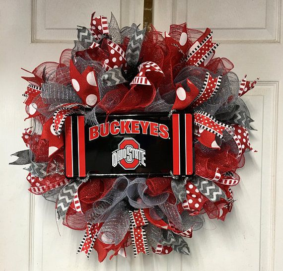 Ohio Statehow your team pride with this Ohio State Football Wreath! The season has begun! Show your team spirit with this Ohio State Buckeye Football Wreath to honor the Scarlet and Grey, right on your front door! This football wreath is a great addition to your Ohio State Buckeye football party decor! Hang it on your door to greet fellow football fans, or lay it flat to make a centerpiece for your table! Measurements are: 28 x 28 x 9 This XL wreath is full and gorgeous with premium scar...