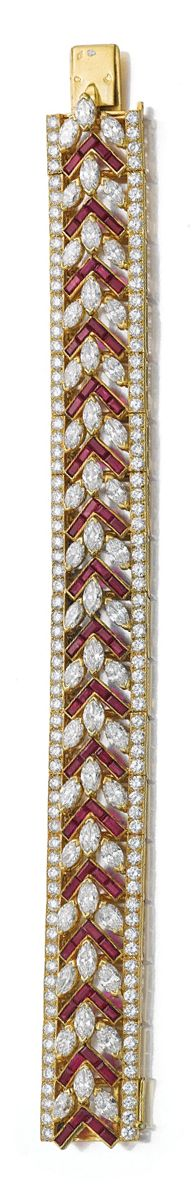 RUBY AND DIAMOND BRACELET, CARTIER.  The open work band of chevron design, set with invisibly-set calibré-cut rubies alternating with marquise-shaped diamonds, set between two lines of brilliant-cut diamonds, length approximately 175mm, signed Cartier