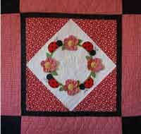 """Ladybug Landing. Ladybugs and Flowers...it's almost as fun as taking a walk in the garden!  This fun quilt is filled with cute ladybugs and dimensional flowers.  With the center set on point, it goes together very quickly.  This quilt measures approximately 39"""" x 39"""". http://www.kayewood.com/item/Lady_Bug_Landing_Quilt_Pattern/2796 $9.00"""