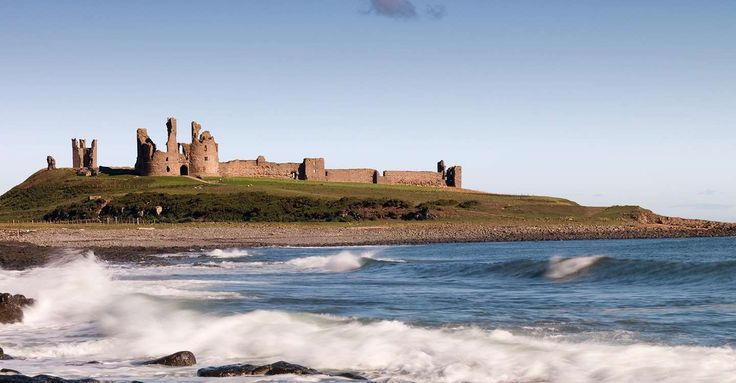 View across the waves towards Dunstanburgh Castle