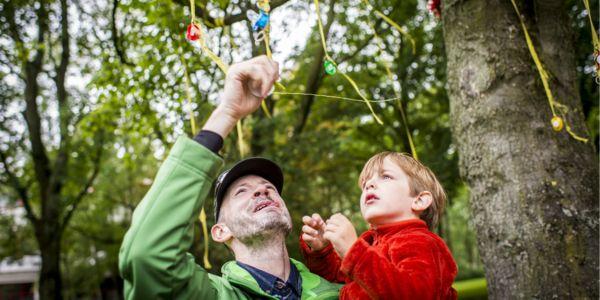 Vader en zoon hangen een tutje aan de boom. Tutjesboom in Park Brilschans