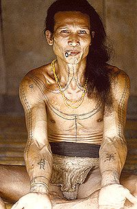 Aman Ipai has many tattoos, including a crucifix-like crab tattooed on his right forearm. Crabs are invoked by Mentawai shamans during healing and other rites because they are believed to never die. They can discard their old bodies and obtain new ones or regenerate severed limbs).