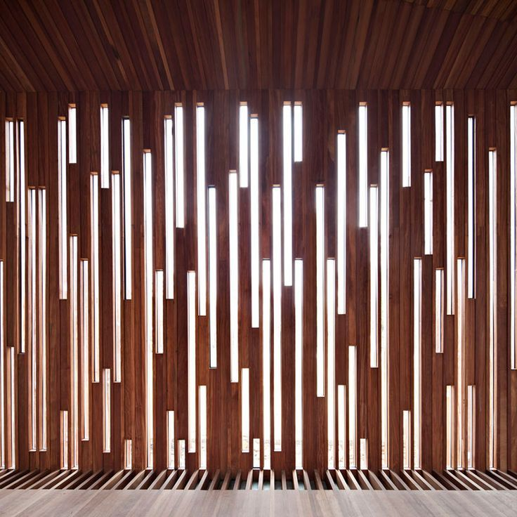 This Patterned Wood Wall is an amazing feature! The combination of the dark red wood panels with the bright white lights looks great! The use of having vertical lines help increase the appearance of height in the room, which is an added bonus! I love how the paneling blends straight into the ceiling and the floor!
