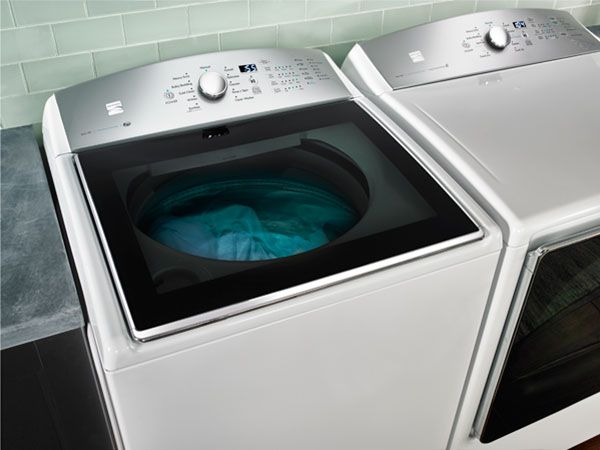looking down on a modern-looking, white and silver, washing machine looking through a smoked-glass top to see blue clothes being washed