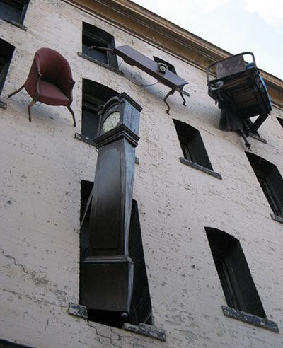 """Since 1997, the building known locally as ""The House of Falling Furniture"" located at the corner of 6th st. and Howard st. in San Francisco, has been a sculptural mural.The piece consists of sometimes malshapened tables, chairs, lamps and even a grandfather clock, all hanging precariously out of the building's windows."