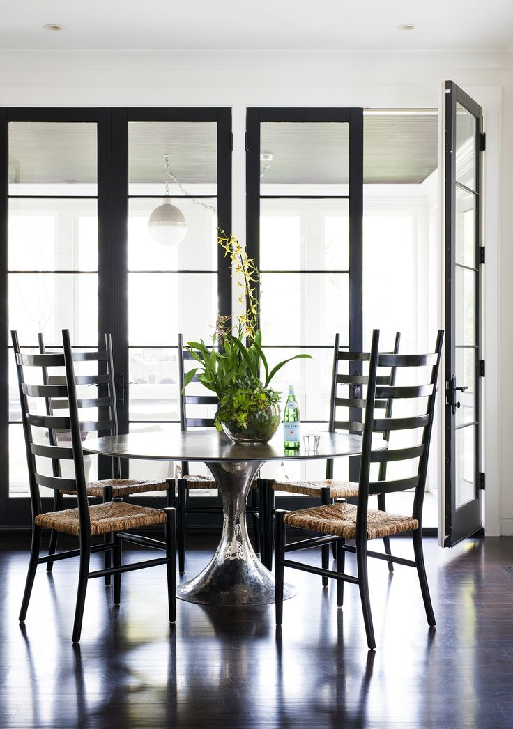 Modern chic breakfast dining area with tall black French doors. Design by Ella Scott Design. Come see the dramatic Before & After: Fussy Traditional to Urban Chic! #breakfastroom #kitchen #blackandwhite #modern #urbanchic #blackdoors #benjaminmooreblackpanther