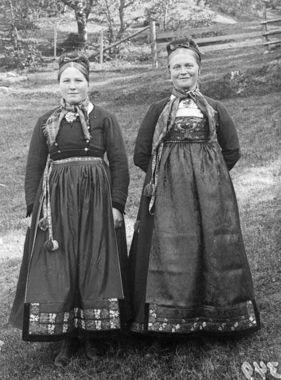 """Begge jentene går i folkedrakter fra Tinn, men jenta til høyre har spor etter den eldre draktskikken (som var vanlig i første halvdel av 1800-tallet.) Her er livhøyden høyere, slik som i Empiremoten på 1820-30-tallet. Denne bunaden heter i dag """"Bunad fra Tinn, Skjælingskleda"""". Hun har imidlertid lue på seg, noe som først ble vanlig etter at den yngre draktskikken kom. Jenta til venstre har lue og trøye etter denne yngre folkedraktskikken i annen halvdel av 1800-tallet, da formen på livet…"""
