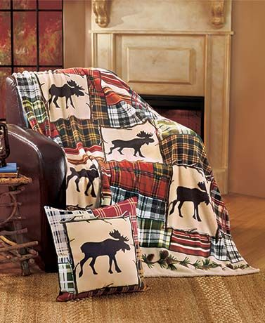 """Add comfort and a decorative touch to your home with this Moose Lodge Throw or Pillow. The 50"""" x 60"""" fleece throw features a silhouette of a moose accented by different patches of plaid. Images of pine cones and branches trim each end."""