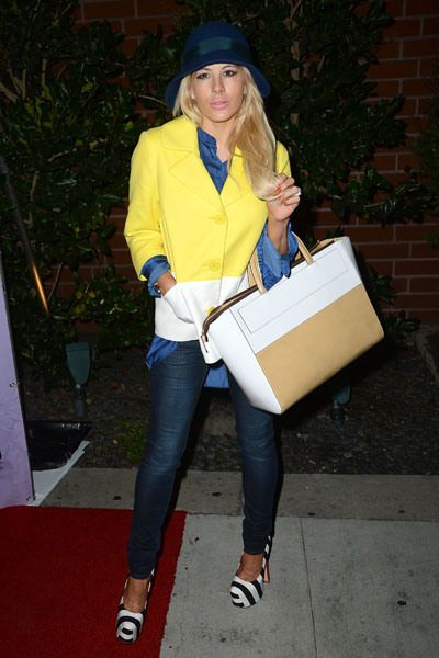 Shayne Lamas looks like she's auditioning for a Real Housewives part in this pretty conservative outfit. We do like the bright yellow and white jacket and black and white striped heels. This is a fun way to dress up jeans.