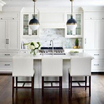 Soft White Kitchen With Marble Subway Tile Backsplash Cabinets Topped Crown Molding A Custom Panel To Cover Range Hood Nailhead Trim Counter Stools