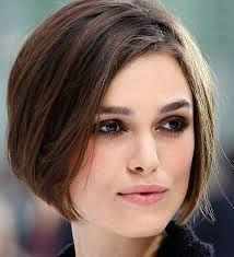 Ce subtil carré court et plongeant a été séparé sur le côté, libérant une grande partie du front de cette femme. Ses cheveux brun foncé encadrent son visage, s'arrêtant à la hauteur du menton. Le cou est entièrement dégagé.