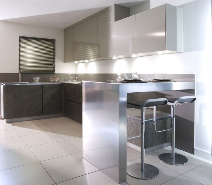 Urban Style Gold Green stone effect and champagne lacquer handle-less units with ceramic worktop and stainless steel breakfast bar.