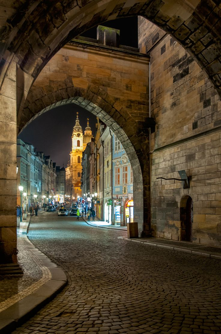 The streets of Prague nightlife - night view of the street through an archway in Prague