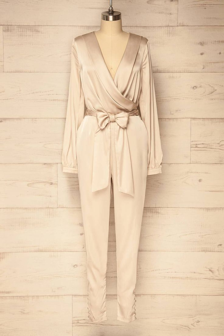Tavila Light / Step out in style and elegance with this fabulous jumpsuit! The stretch satin material is smooth, while the loose fit is comfortable. The plunging cross neckline and removable fabric belt will show off your silhouette. Featuring button closures at the wrists and ankles, pockets, and an invisible back zipper, this piece is easy to slip on and a joy to wear, no matter the occasion! #boutique1861