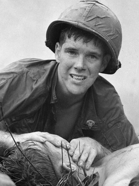 Medic with the 1st Infantry Division (Lai Khe),James E. Callahan of Pittsfield, Mass., looks up while applying mouth-to-mouth resuscitation to a seriously wounded soldier north of Saigon in June 1967.