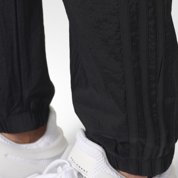 Blending Berlin street fashion with tech-influenced touches, these men's track pants update '90s style with mod details.  Sleek tonal details include 3-Stripes down the sides, as well as a Trefoil logo that rests on the left hip. The front pockets hold essentials during urban adventures. Tapered legs give the pants a modern cut, while hook-and-loop closures at the cuffs complete the street-ready design.