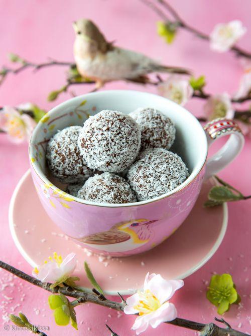 """Raakasuklaa kookospallot  Raakaleivonta on tullut lähemmäs tavallista jauhopeukaloa, kun perusraaka-aineet ovat hivuttautuneet isompien ruokakauppojen valikoimiin. Raakasuklaa sisältää yksinkertaisimmillaan vain raakakaakaojauhetta, kaakaovoita/kookosöljyä ja hieman makeutusta. Ravintoarvojen vuoksi tykkään kuitenkin """"leipoa"""" mukaan myös pähkinöitä ja manteleita. Mitä enemmän kuivia aineita sitä tahnamaisempaa seoksesta tulee. Pallerot ovat helppoa hyvän mielen herkkua."""