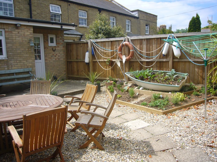Seaside garden using reclaimed and painted boat as a herb for Nautical themed backyard
