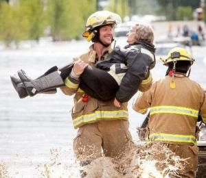 This photo of Nanton firefighter Wiebe with a big smile was snapped as a he carried a High River flood victim to safety as the water rose up around them.