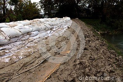 Sandbags flood protection on a muddy levy with trail made from wooden planks on a rainy day