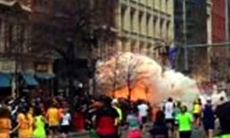 In this image from video provided by WBZ TV, spectators and runners run from what was described as twin explosions that shook the finish line of the Boston marathon.