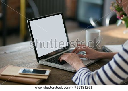 Close up of a woman sitting in front of her portable computer empty screen with coffee, phone at table and hands at keyboard in the room. Distance learning or work from home concept. Laptop mockup