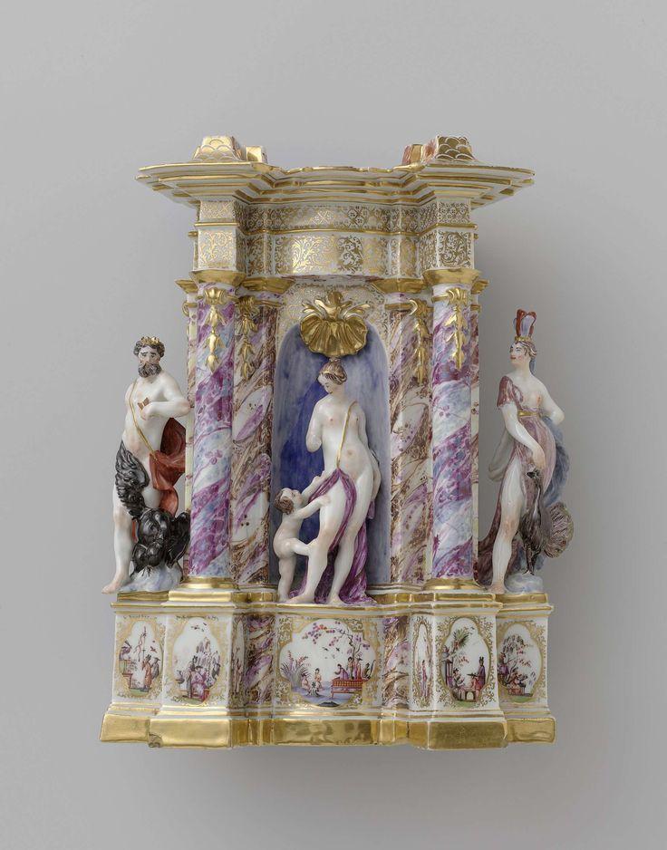 Meissener Porzellan Manufaktur | Temple of Venus, Meissener Porzellan Manufaktur, Johann Gottlieb Kirchner, 1727 | Beeld van beschilderd porselein. Het beeld stelt een Venustempel voor. Voor een wand staan twee zuilen die een verkropt hoofdgestel dragen. In de wand bevindt zich een nis waarin een Venus met Amor is geplaatst. Links en rechts van de wand staan op hoge postamenten resp. Jupiter met een zwarte adelaar en Juno met een pauw. Het beeld is niet gemerkt.