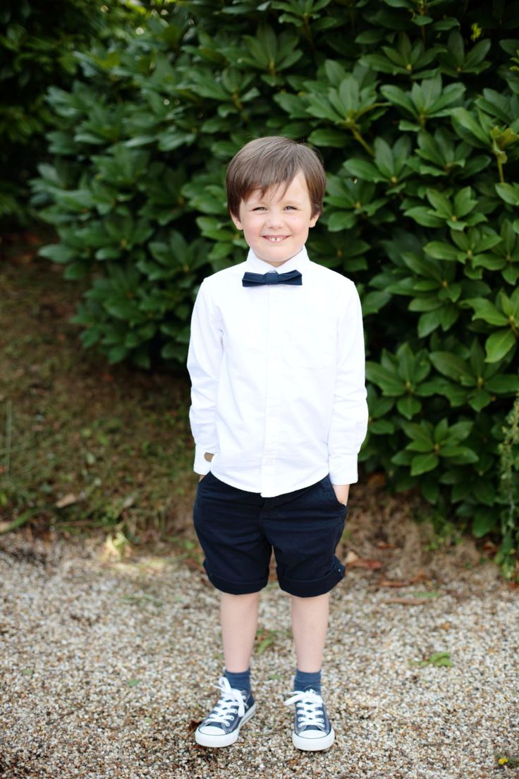 Page boy in shirts, trainers and bow tie - Image by Dasha Caffrey - Rustic Wedding With Tartan Accents And Bride In Elegant Gown From Go Bridal With A Sassi Holford Veil And Rachel Simpson Shoes With Groom And Groomsmen In Kilts