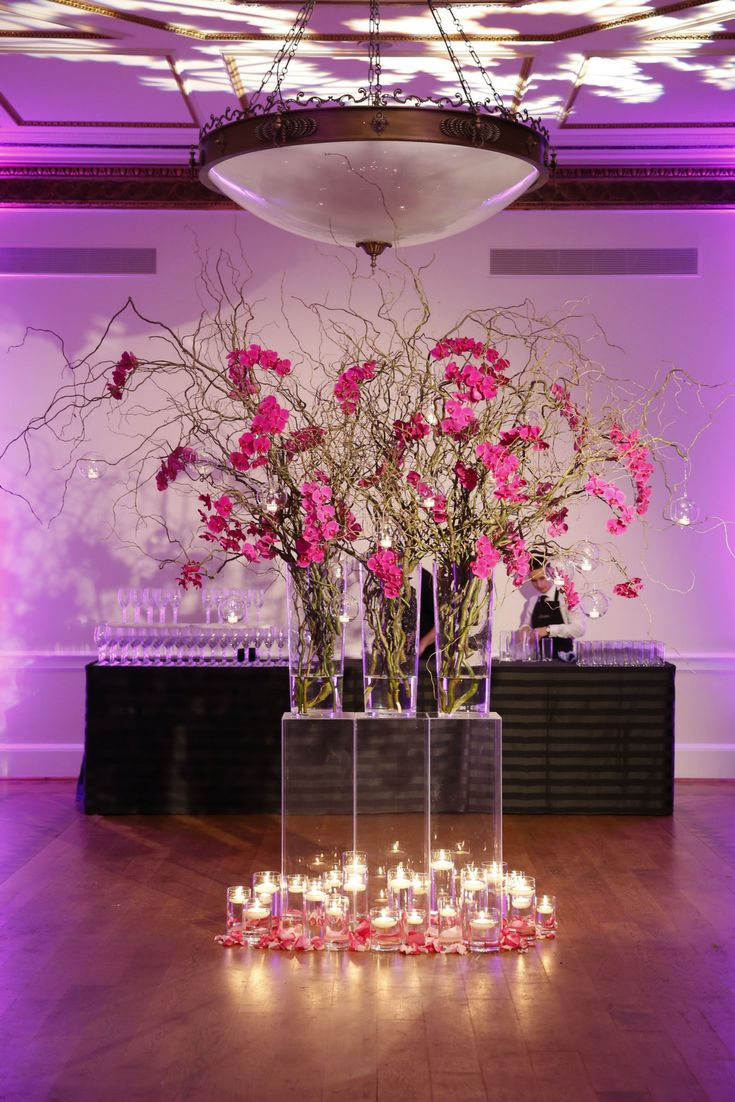 Stunning flower arrangement with pink flowers, clear perspex plinths and plenty of candles. You can never have too many candles! Purple lighting adds the finishing touch at Kent House Knightsbridge