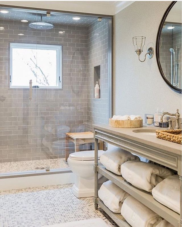 like the simplicity of this bathroom and how the pebble floor is followed into the shower floor.  Designed by Brooks and Hill #interiordesign #bathroom #subwaytile #openvanity #kedrachalendesign