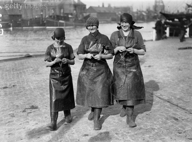 herring girls with aprons walking and knitting