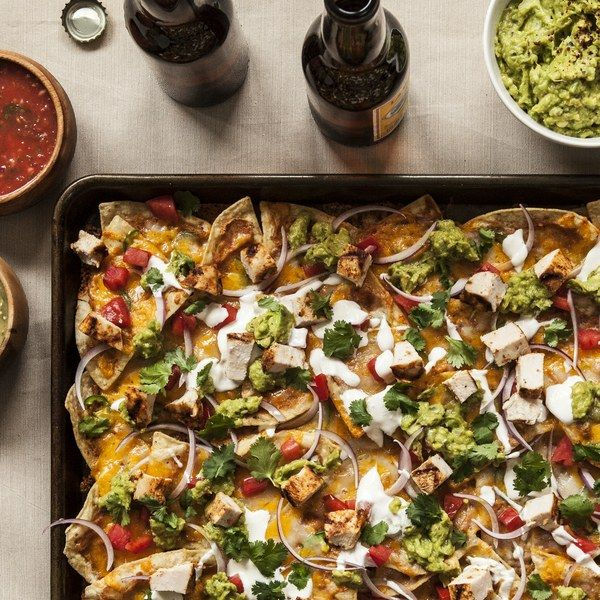 """Inspired by my mom Julie Boone, the family's """"Nacho Queen,"""" these nachos start with three essential ingredients: a dollop of homemade pinto bean dip, sliced jalapeños, and plenty of grated cheddar. The key to crispy nachos is to limit the number of ingredients that go into the oven with the chips.                  This simple yet solid foundation is delicious on its own and provides a great canvas for your favorite fresh toppings."""