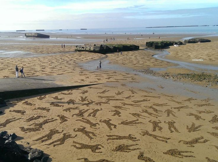 """Tribute to International Peace Day (Sept 21st), British artists Jamie Wardley and Andy Moss of Sand in Your Eye took a team of 60 volunteers to Normandy beach over the weekend to sketch the outlines of 9,000 soldiers figures into the sand. The installation was created to commemorate the people who lost their lives on June 6th, 1944 and is appropriately titled """"The Fallen 9,000."""""""