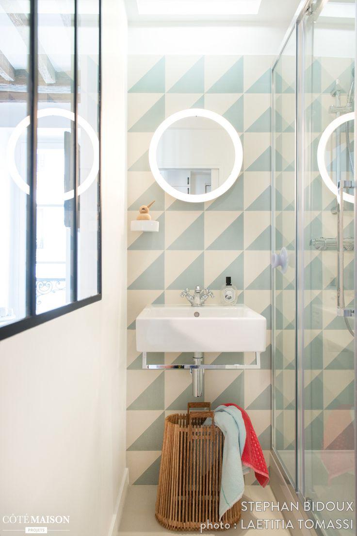 La verrière donne un beau volume à cette petite salle de bains. Le carrelage et le miroir lui apportent un aspect graphique