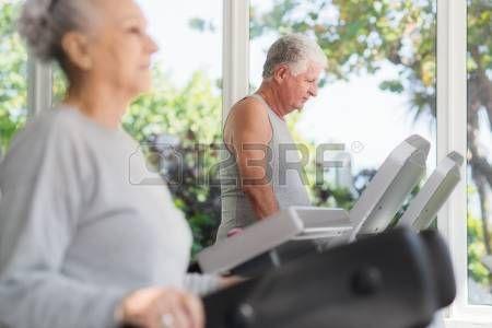 Les gens et les sports, couple de personnes �g�es de travailler sur tapis roulant en salle de gym de remise en forme photo