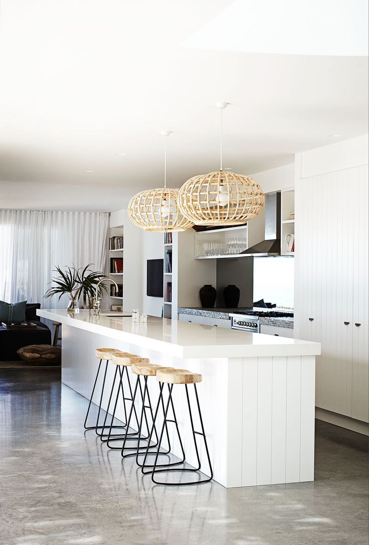 """Smaller versions of the cane pendant featured in the dining area combine with timber panelled kitchen cabinetry, by Haughey Group, to add to the beachy feel. """"We didn't want slick, smooth surfaces so this also helped bring in texture,"""" the homeowners say. The Sled bar stools are from [Les Interieurs](http://www.lesinterieurs.com.au/