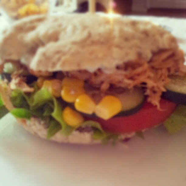 Burger with chicken with barbeque sauce, tomato, cucumber, corn and salad